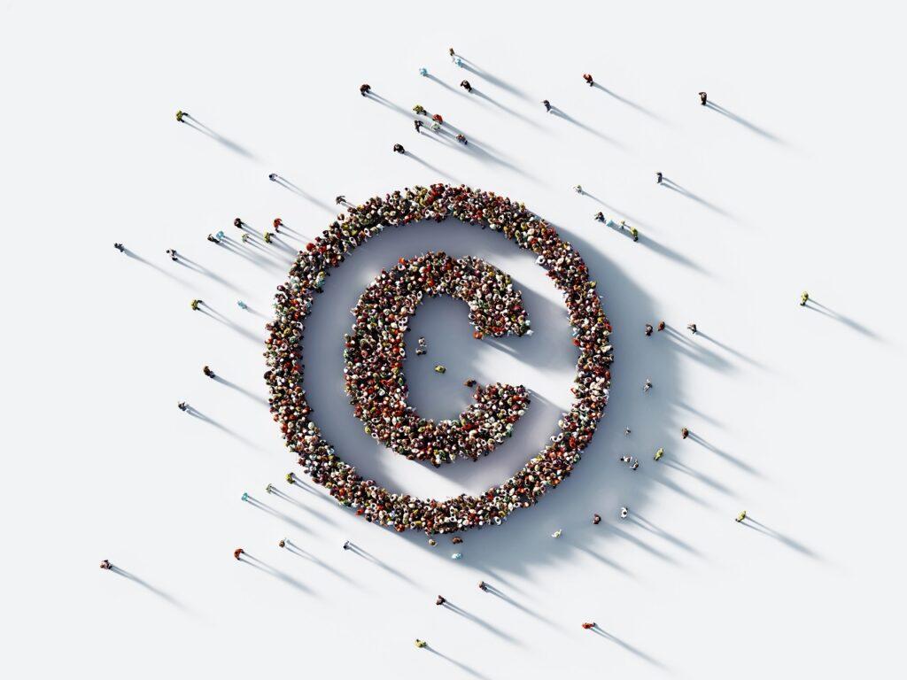 Een grote groep mensen vormen samen het logo van copyright